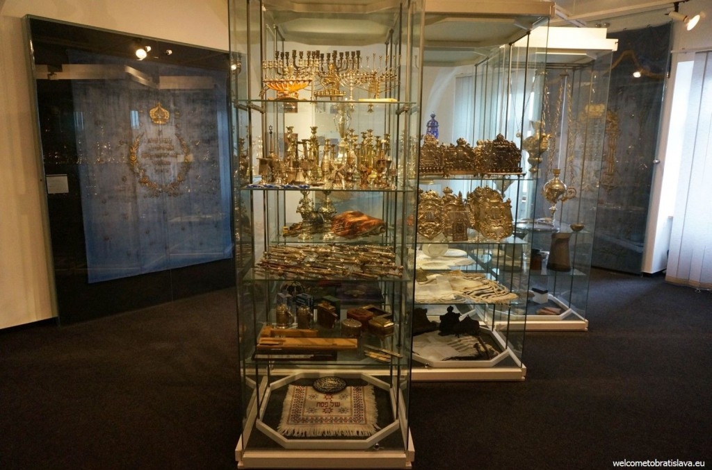 Metal candlesticks are displayed in glass showcases