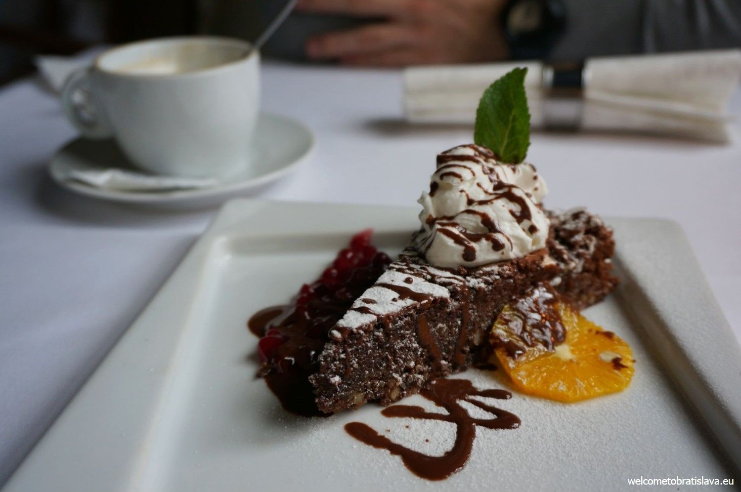 Chocolate & almond cake served with fruit and whipped cream