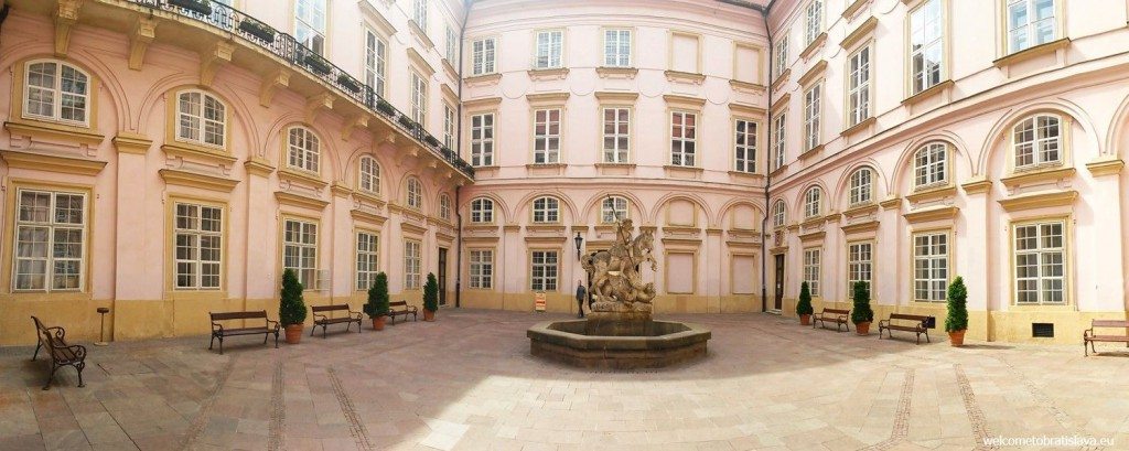 The courtyard with a fountain and a statue of St. George