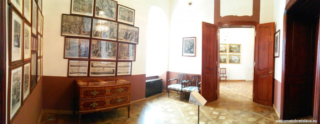 The first floor with the original wooden wall-panelling and paintings