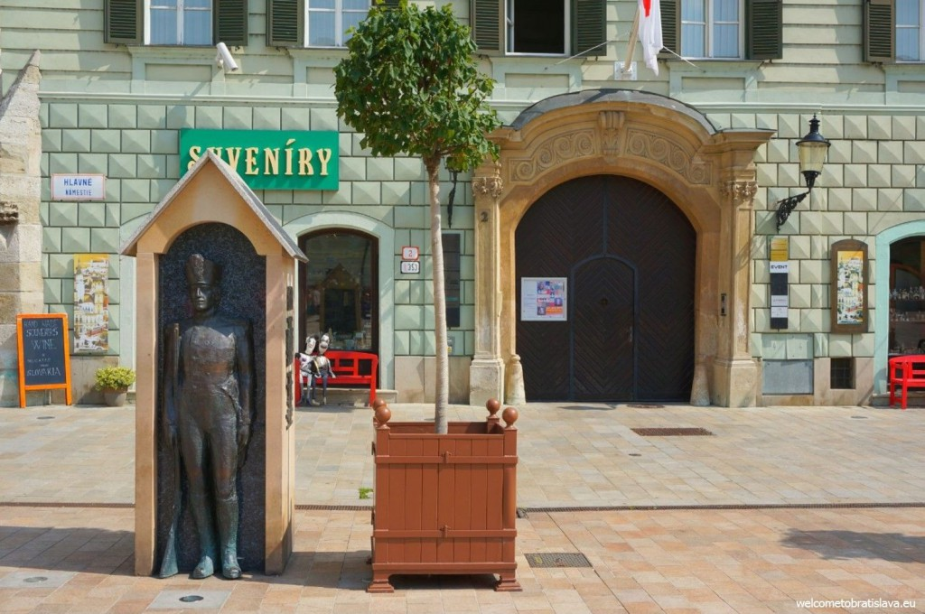 Napoleon's friend is standing in front of a souvenir shop at the Main square