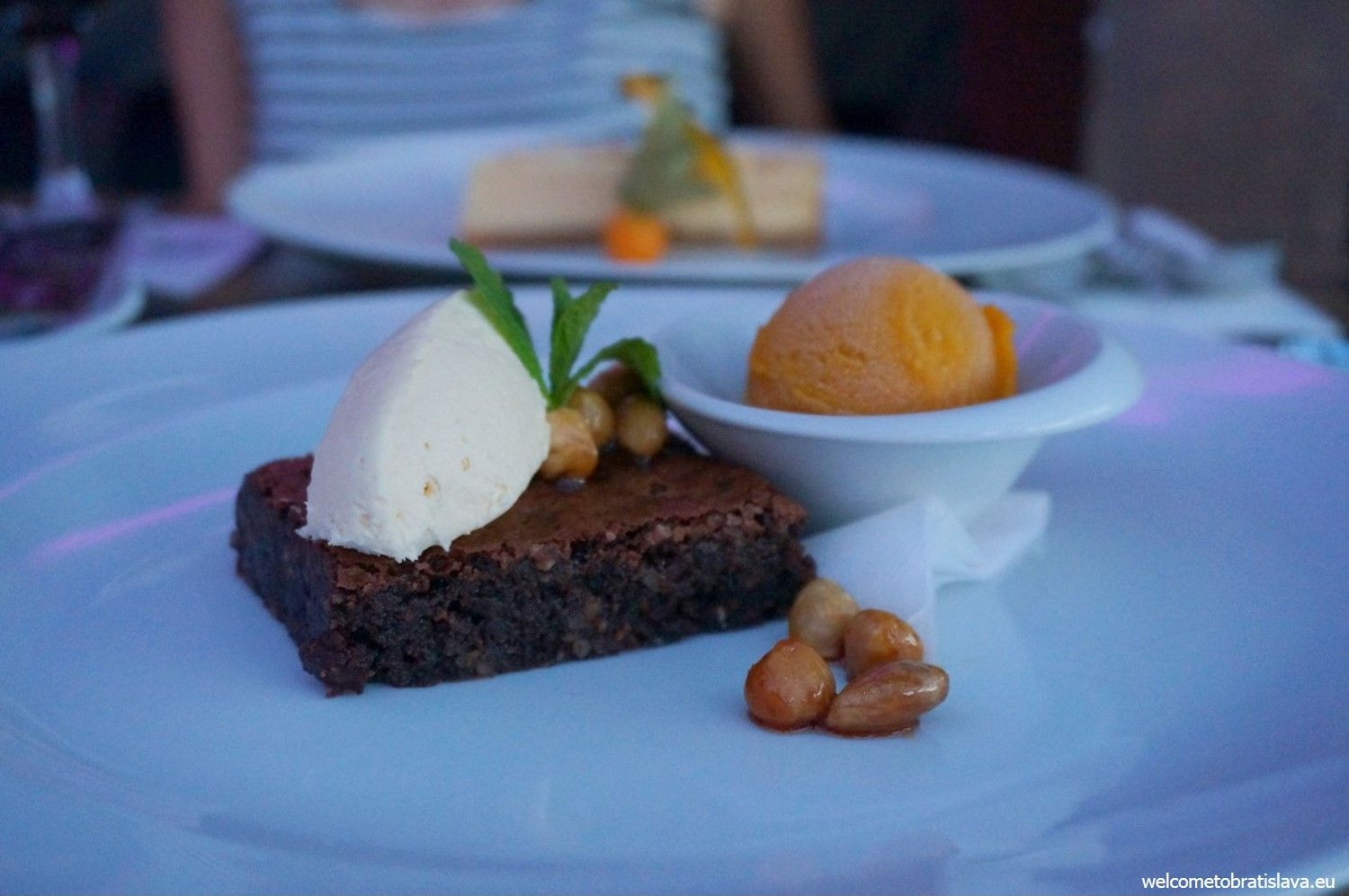 Dark chocolate brownie with a white chocolate mousse, caramelized nuts and mango sorbet