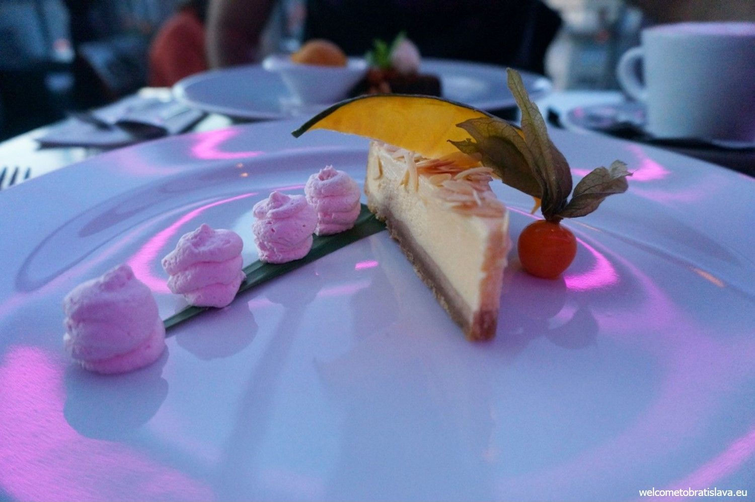 A mango cheesecake with almonds and sauce of coconut milk and lyche