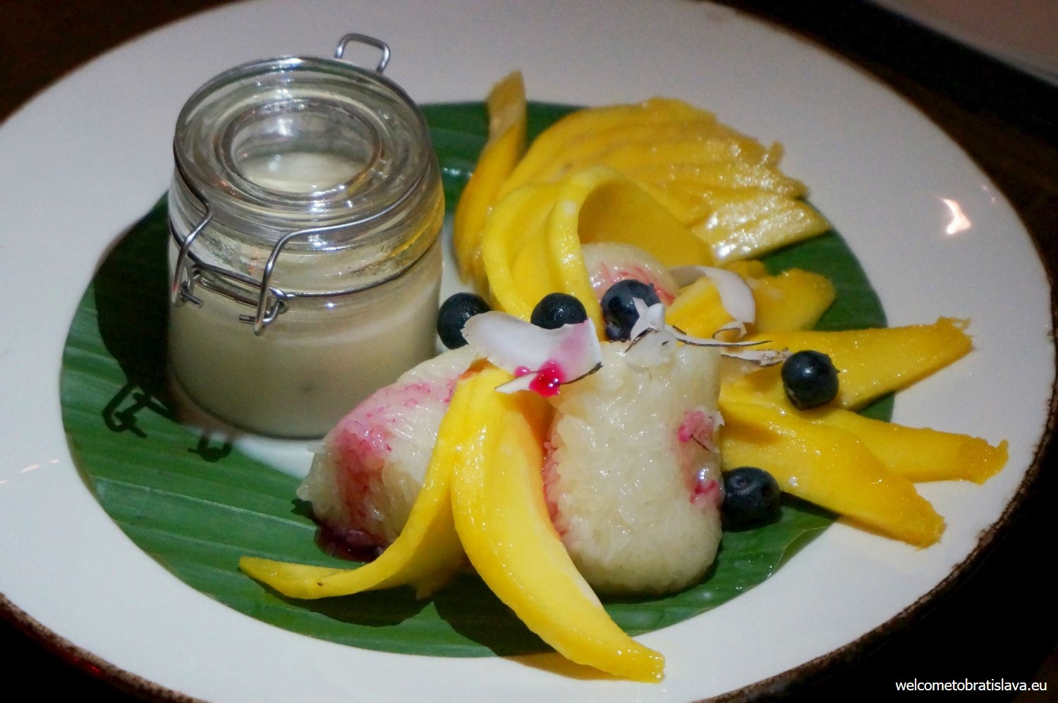 A delicious dessert - white sticky rice with mango, coconut and blueberries