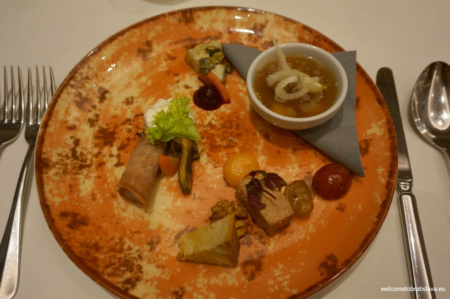 A cold veal and pork jelly served in a soup bowl with vinegar and onion
