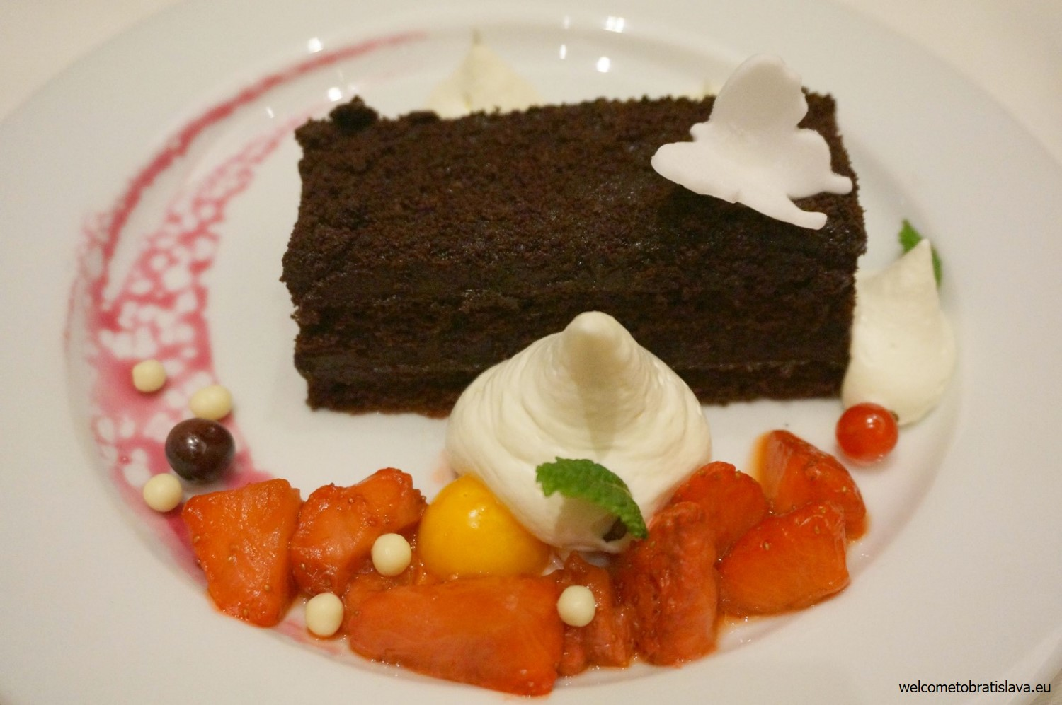 Carlton cake served with vanilla whipped cream, ambéed fruit applesauce and marinated cranberries